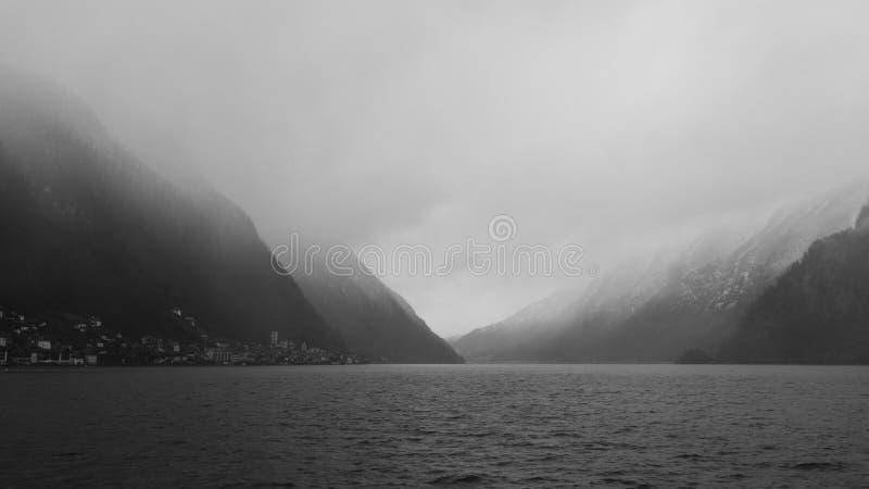 Hallstatt en omringende bergen in Oostenrijk omvat door de mist op een de winterdag royalty-vrije stock fotografie