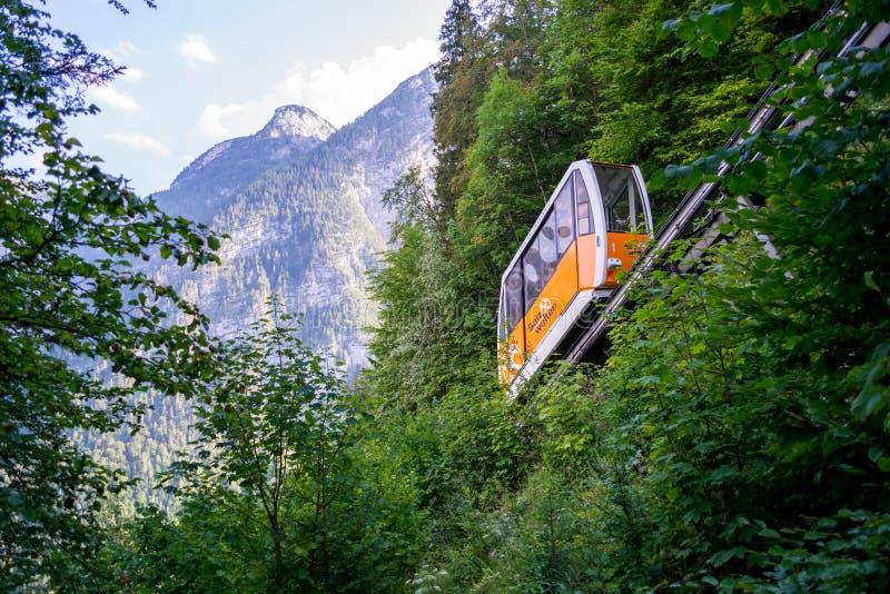 Hallstatt, Oberosterreich / Austria - August 19, 2018: An orange cable car going up the rails to the salt mine above Hallstatt royalty free stock photo