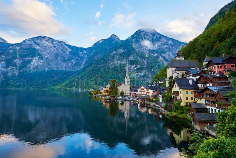 Hallstatter湖风景看法有一条小船的在奥地利阿尔卑斯 在Hallstatt湖的秋天日落有美丽的云彩和反射的 库存照片