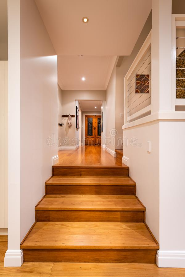 Hallway with hard wood flooring in luxury domestic home lit with down lights stock image