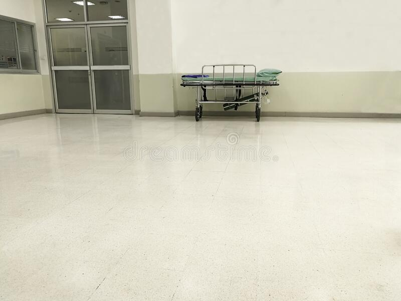 Hallway infront of emergency room ward in hospital with nobody on bed. White clean floor and hygiene care in clinic stock photo