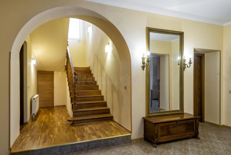 Hallway with mirror, lamps and wooden stairs royalty free stock image