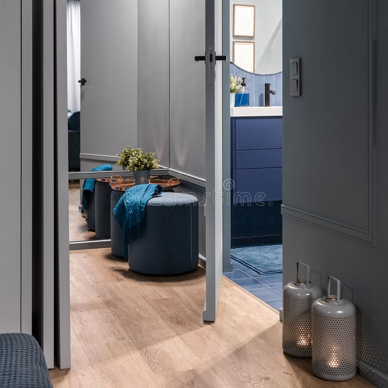Hallway with open bathroom door. Stylish home hallway interior in blue with open bathroom door royalty free stock photos