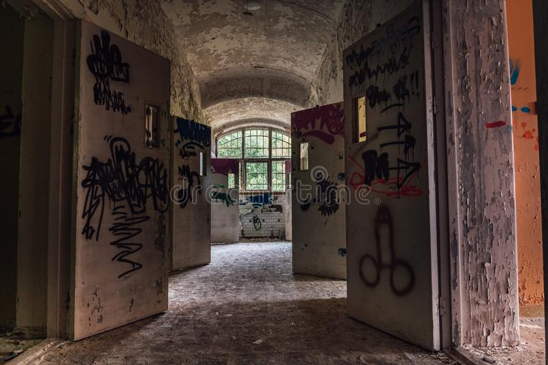 Hallway with open doors from an abandoned mental institution royalty free stock image