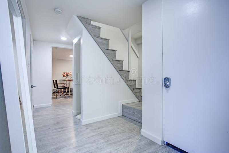 Hallway with pure white walls and gray hardwood floor.  stock images