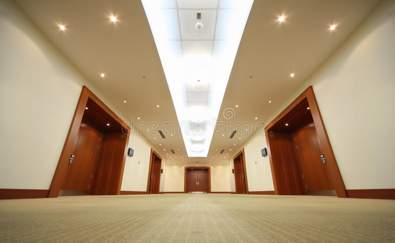 Hallway with wood doors, door at end of corridor stock images