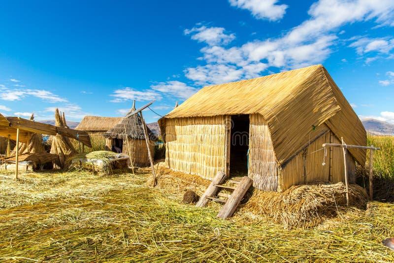 Halmtäckt hem på att sväva öar på sjön Titicaca Puno, Peru, Sydamerika. Tätt rota att växter Khili arkivbilder