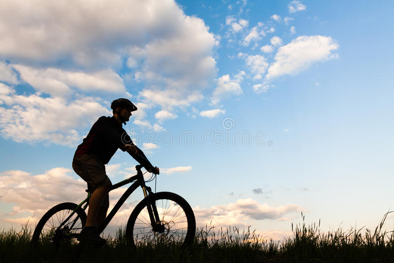 Halna rowerzysty kolarstwa sylwetka nad niebieskim niebem zdjęcie stock