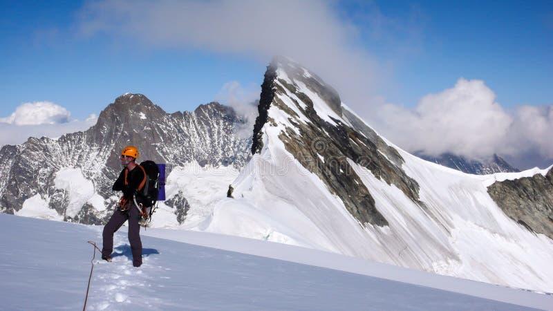 Halnego arywisty pozycja na lodowu i patrzeć cudowną góry panoramę wokoło on i krajobraz zdjęcia stock