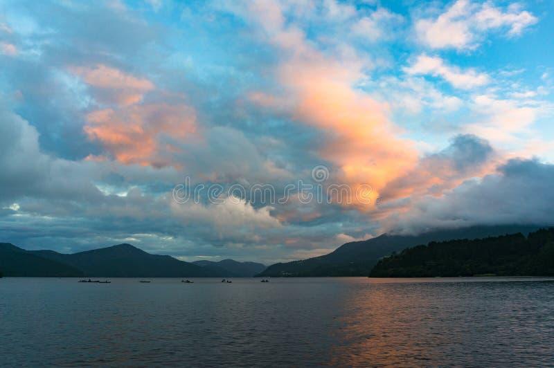 Halny jezioro na wschodzie słońca z łodziami rybackimi w odległości fotografia stock