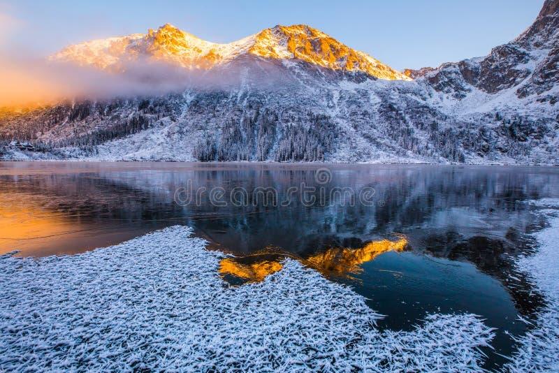 Halny jezioro przy wschodem słońca Jasny lód zakrywający jezioro w górach obraz stock