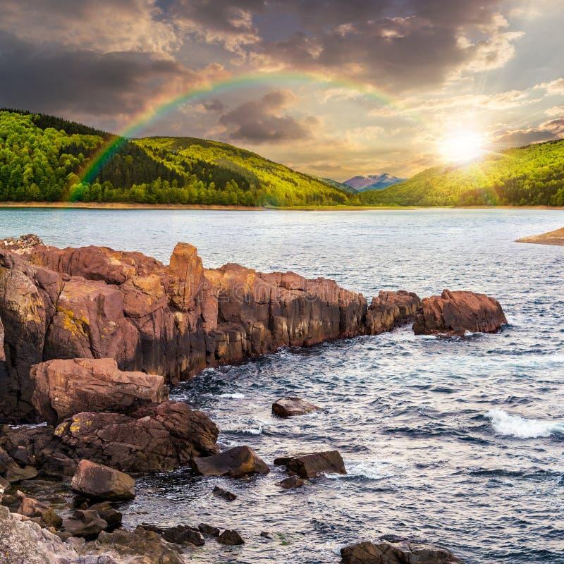 Halny jezioro z skalistym brzeg przy zmierzchem zdjęcie royalty free