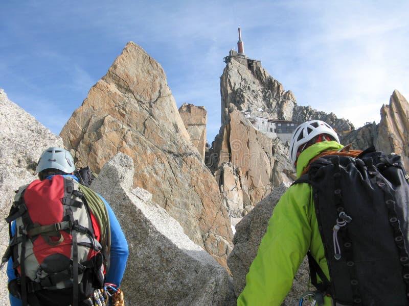 Halny przewdonik i męski klient na skalistym grani kłoszeniu w kierunku wysokiego szczytu w Francuskich Alps blisko Chamonix obrazy stock