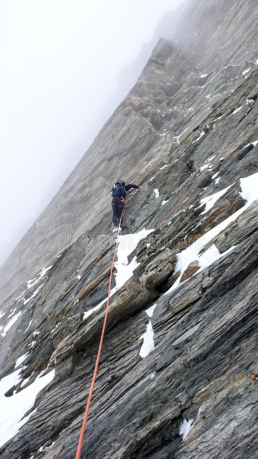 Halny przewdonik prowadzi stromą rockowego pięcia smołę na ciężkiej mountaineering trasie w Alps na chmurzącym i mgłowym dniu obraz royalty free