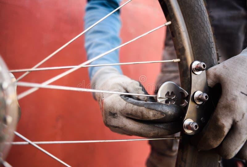 Halny rowerowy naprawianie Mechanik przy pracy naprawiania roweru szprychami fotografia royalty free