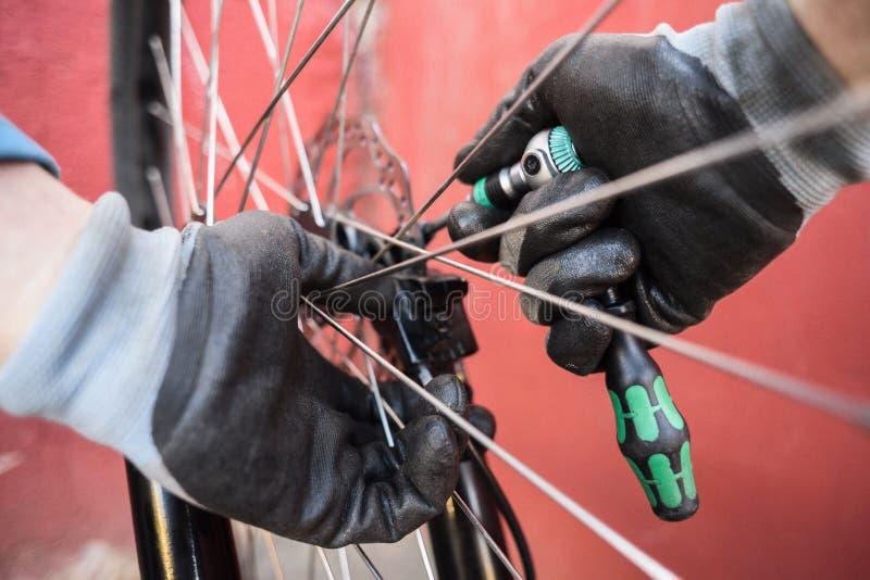 Halny rowerowy naprawianie Mechanik ręki przy pracy naprawiania tyły w obraz stock