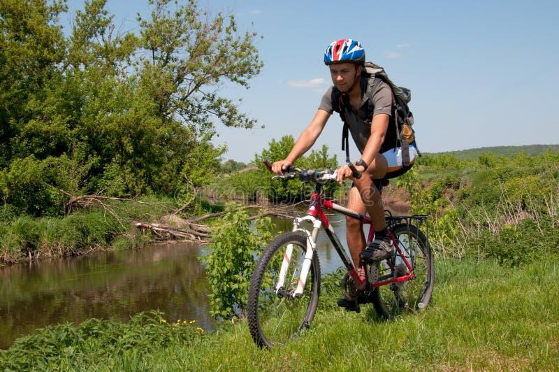 Halny rowerzysta obok pięknej rzeki zdjęcie royalty free