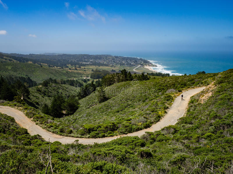 Halny rowerzysta z Montara plażowym i pokojowym oceanem w backg obrazy royalty free