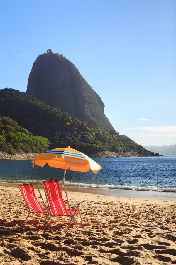 Halny Sugarloaf słońca parasol i krzesła na czerwieni plaży (Praia zdjęcia royalty free