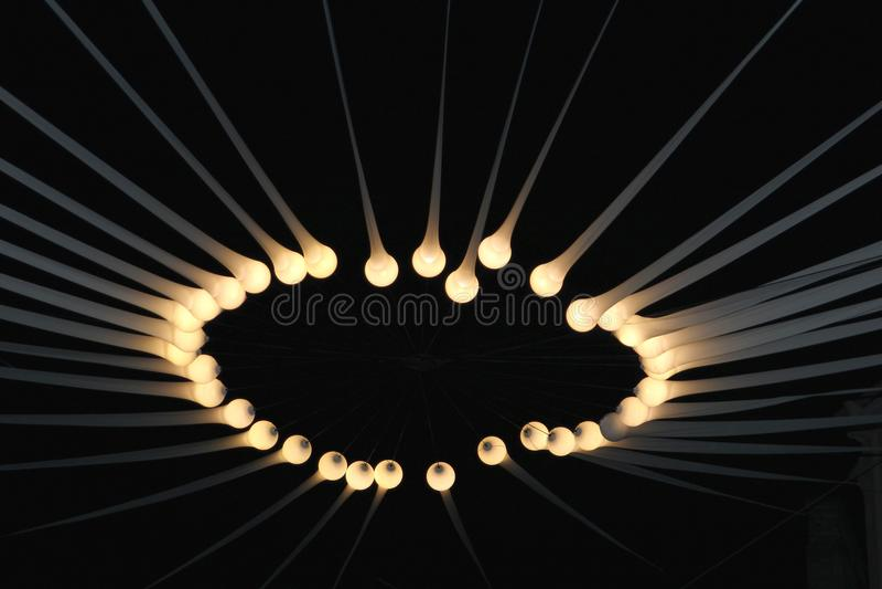 Halo de luzes elétricas e de feixes na escuridão imagem de stock royalty free