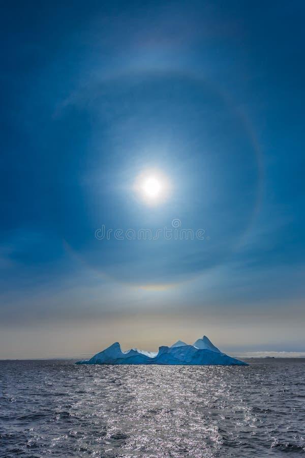 Halo de Sun que brilha sobre o iceberg e o oceano azuis, Greenlan norte foto de stock royalty free