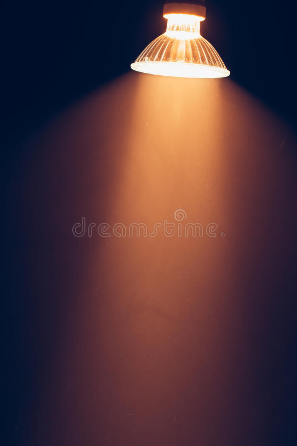 Halogen lamp with reflector, warm light in haze stock photos