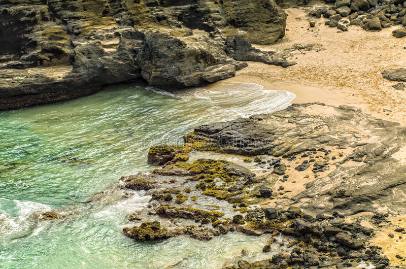 Halona Beach Cove, Honolulu, Oahu Hawaii. Turquoise blue green waters of the Pacific Ocean carve the coastline at Halona Beach Cove on the southeast side of the royalty free stock photos