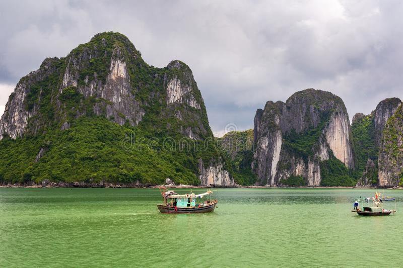 Halong Bay limestone cliffs with two traditional fishing boats, UNESCO world natural heritage, Vietnam. Halong bay limestone cliffs with two Vietnamese stock photo