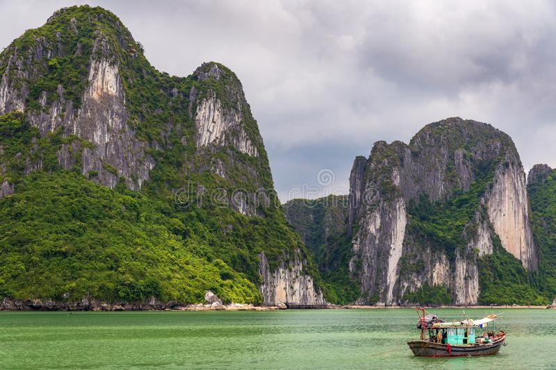 Halong bay limestone cliffs with traditional green fishing boat, UNESCO world natural heritage, Vietnam. Halong bay limestone cliffs with a Vietnamese stock photos