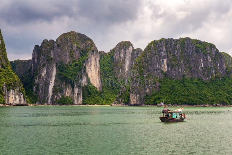 Halong-Bucht-Felsformation mit traditionellem grünem Fischerboot, UNESCO-Weltnatürliches Erbe, Vietnam stockbild