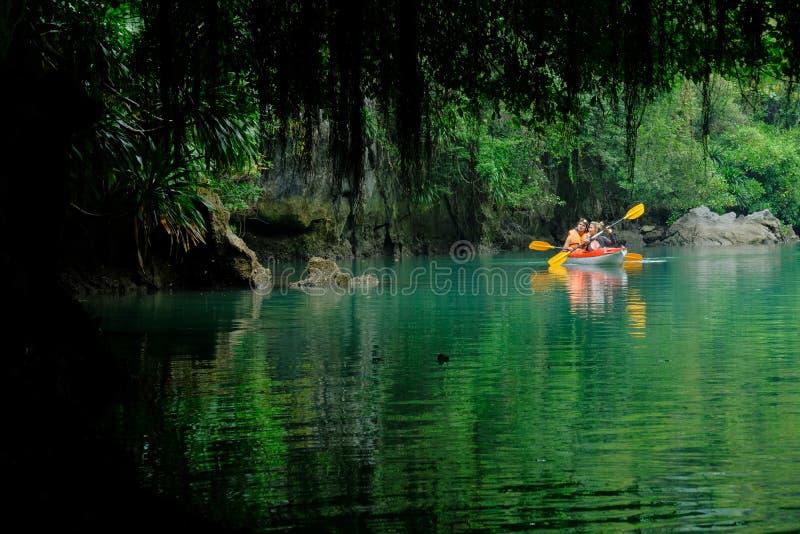 Halong fjärd/Vietnam, 07/11/2017: Två fotvandrare på kajaken som paddlar till och med grottor och tät djungel i den Halong fjärd- royaltyfri foto