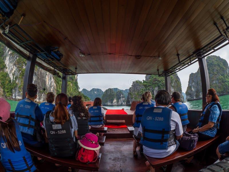 Halongbaai, Vietnam - April 26, 2018: De toeristen in reddingsvesten onderzoeken Halong-Baai royalty-vrije stock afbeelding