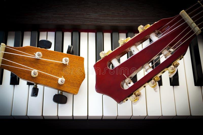 Hals der Gitarre auf Klavier lizenzfreie stockfotografie