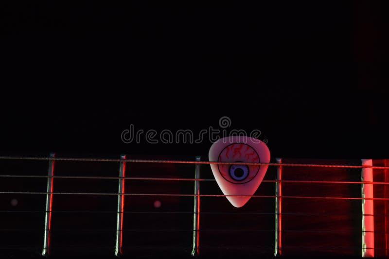 Hals för elektrisk gitarr med en kall gitarrhacka i mörk bakgrund arkivfoton