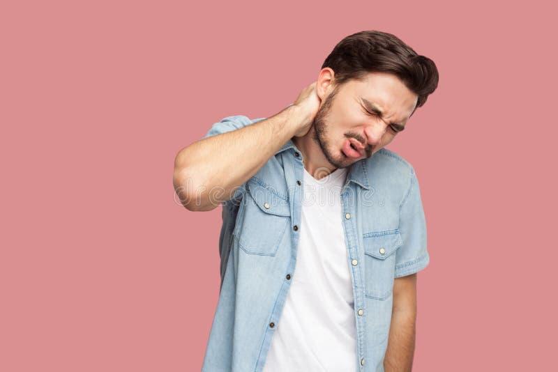 Hals of rugpijn Portret van de droevige zieke knappe gebaarde jonge mens in blauw toevallig stijloverhemd die en zijn pijnlijk be royalty-vrije stock foto