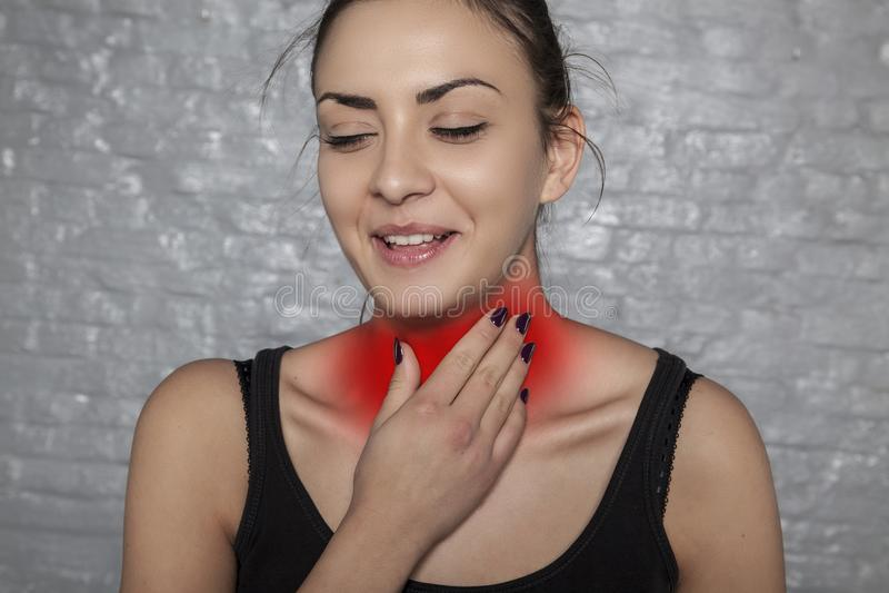 Hals som smittas med bakterier, en kvinna som rymmer hennes hals arkivbild
