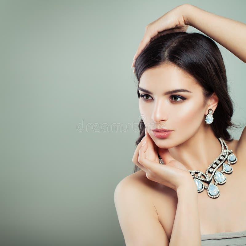 Halsband för smycken för ung brunettkvinna bärande royaltyfria bilder