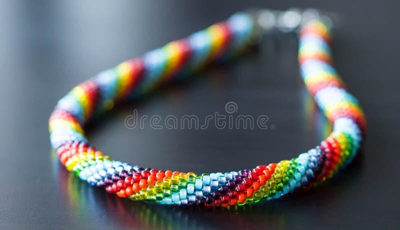 Halsband från mång--färgade pärlor på en mörk bakgrund royaltyfri bild