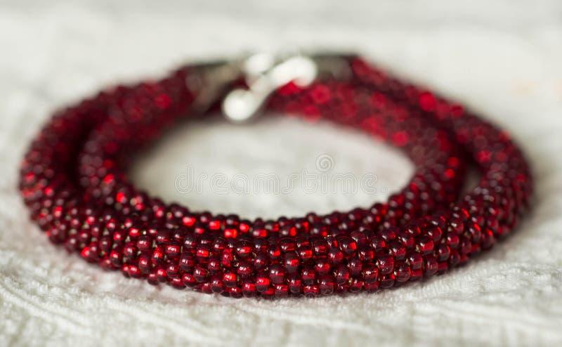 Halsband från röda pärlor på en textilbakgrund arkivbilder