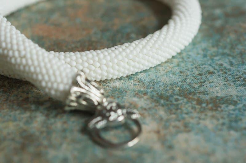Halsband från vita pärlor på en textilbakgrund arkivbild