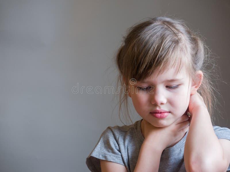 Halsen smärtar Ståenden belastade det olyckliga barnet som flickan med baksida smärtar, negativ mänsklig sinnesrörelseansiktsuttr arkivbild