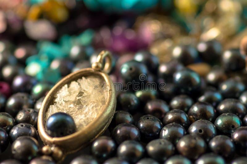 Halskette auf einen Stapel schwarze Perlen stockbilder