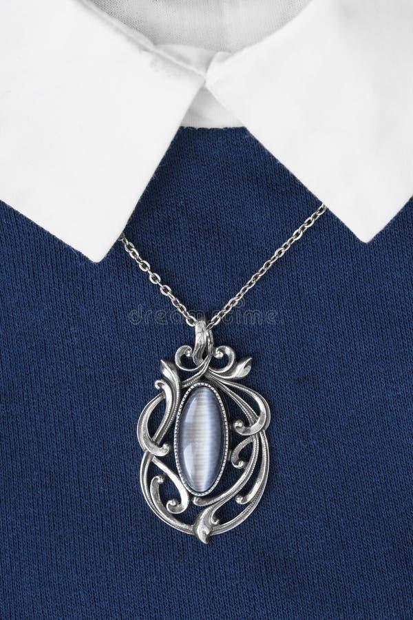 Halskette auf Pullover stockbilder
