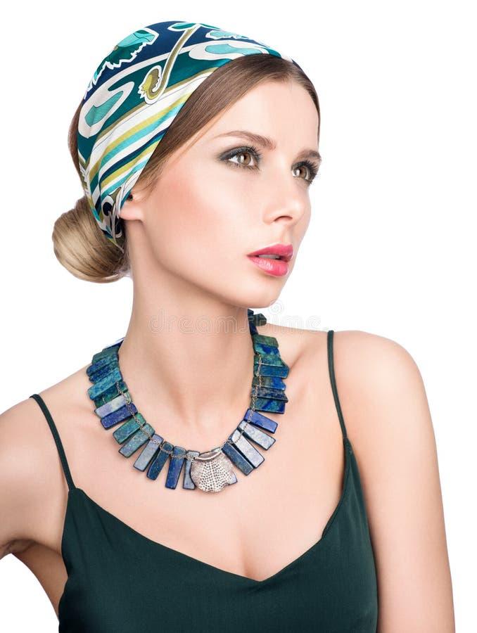 Halskette und Haar mit einem Kopftuch Schönheitsporträt der jungen Schönheit in einem dunkelgrünen Kleid lizenzfreie stockbilder