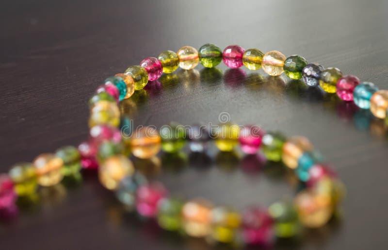 Halskette von den Glasperlen von verschiedenen Farben auf einer dunklen Oberfläche stockbild