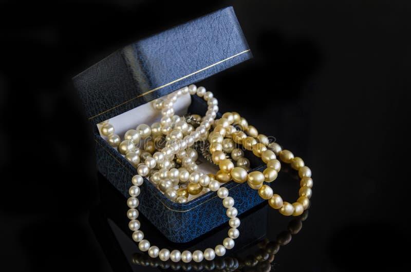Halskette von weißen und gelben Perlen in einer blauen Schatulle stockfotografie