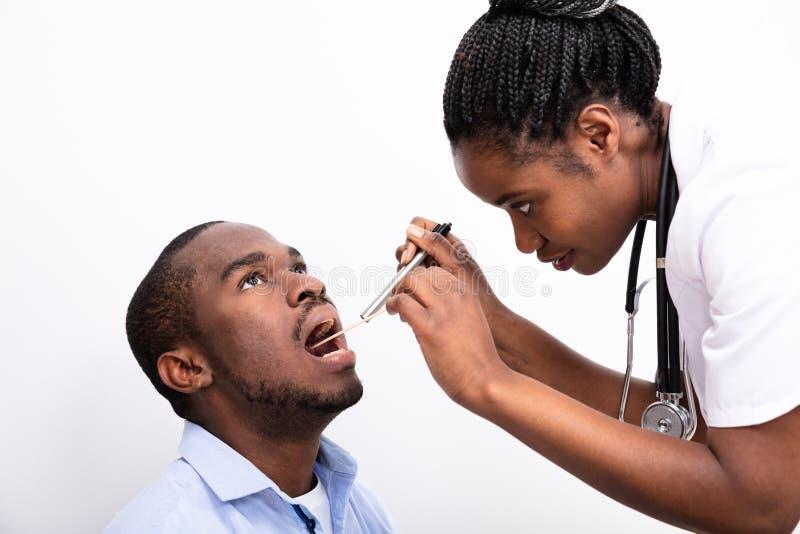 Halsschmerzen Doktor-Checking Mans lizenzfreie stockbilder