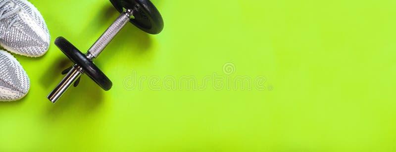 Haltère étendue plate, espadrilles grises de sport sur le fond vert clair Disposition avec l'équipement de forme physique et espa photo stock