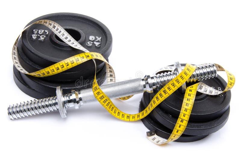 Haltère avec des poids et le ruban métrique images libres de droits