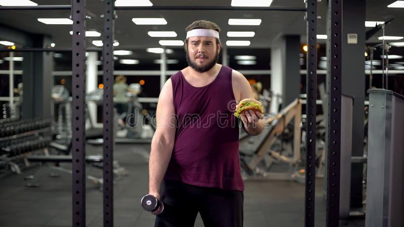 Haltère d'homme obèse et hamburger de levage de juger disponible, décision de la vie, motivation images stock